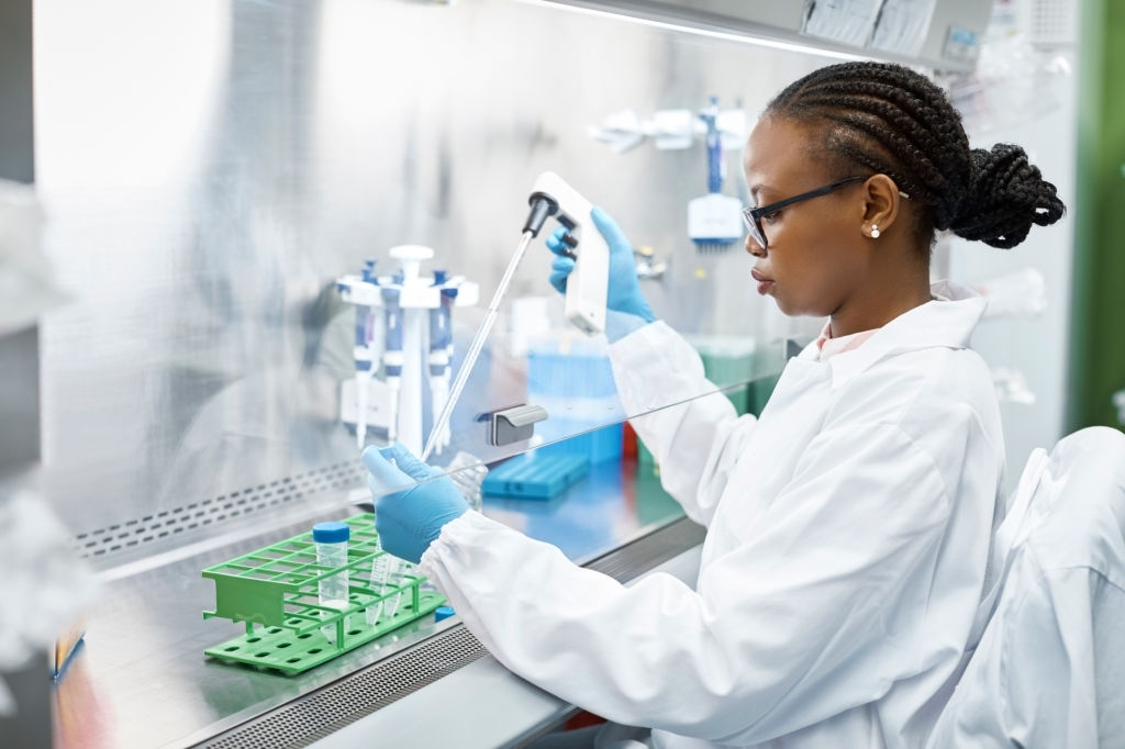 Female scientist analyzing medical sample in test tube. Young researcher is wearing lab coat. She is concentrating while working in laboratory.